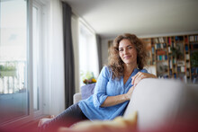 Smiling Woman Sitting On Sofa By Window At Home
