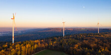 Wind Turbines Standing In Autumn Forest At Dusk