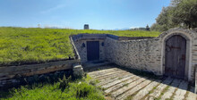 House Or Bunker Built Of Stone Underground With Solid Wood Door And Natural Grass Roof