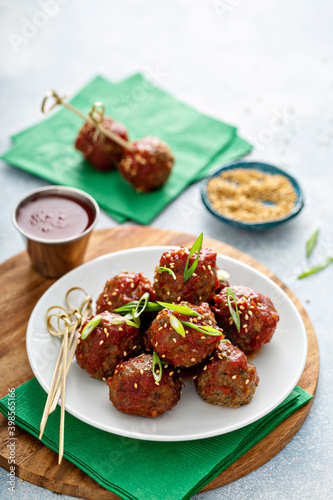 Slika na platnu Asian meatballs appetizers with sweet and sour sauce and wooden skewers