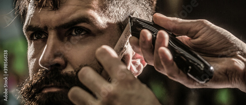Hands of barber with hair clipper. Haircut concept. Hipster client getting haircut. Man visiting hairstylist in barbershop