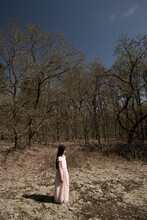 Girl In Long Dress Standing And Dreaming In Bare Scrub Bush In The Dunes In Early Spring