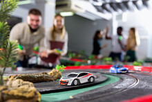 Slot Colorful Car Racing Track. Emotional Players Drive Toy Cars In The Background