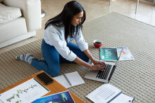 Mixed Race Woman Sitting On Floor Using Laptop Working At Home