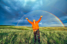 Elderly Man Tourist Raised His Hands Up And Rejoice At The Big Rainbow Over The Steppe Spring Day