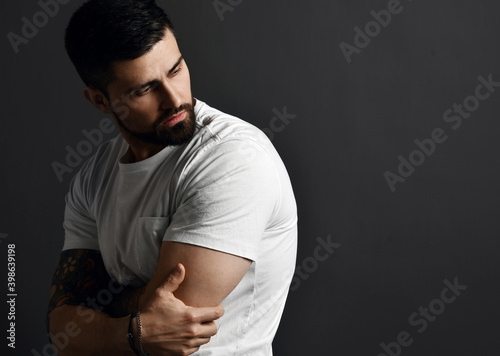 Canvastavla Handsome modern brutal bearded muscular man in t-shirt and with tattoo on arms stands side to camera looking back at copy space over grey background
