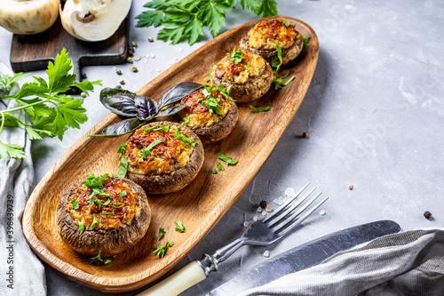 Baked stuffed mushrooms on a wooden plate and gray background, top view, copy s Tapéta, Fotótapéta