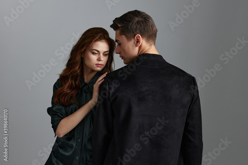 Fotografía man hugs pretty woman on gray background back view