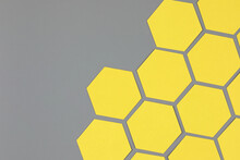 Trendy Abstract Diagonal Geometric Composition With Bright Yellow Paper Hexagons On Neutral Gray Background With Copy Space For Text. Flat Lay, Top View. Year Color Trend