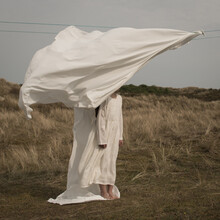 Girl In White Dress Standing Behind Sheet On Laundryline In The Wind In Nature