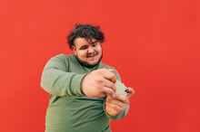 Funny Charismatic Young Obese Guy Is Having Fun Playing Games On His Mobile Phone Device, A Man Is Excited And Cheerful, Totally Concentrated On The App, Standing On A Red Background.