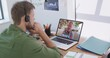 Caucasian man on laptop video chat wearing phone headset at home