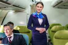 Portrait Young Woman In Blue Suit, Flight Attendant/air Hostess In Business Class Cabin At Airplane..