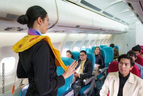 Photo Asian Air hostess staff airline demonstrate safety procedures to passengers prior to flight take off in cabin airplane