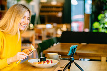 Blond Female Blogger Holding Fork And Knife. Woman In Modern Cafe Interior Eating Cottage Cheese Pancakes Or Traditional Syrniki With With Raspberries Jam With Yogurt. Healthy Breakfast Concept.