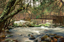 Water From The Reservoir Going Down The River Among Stones And Passing Under A Small Wooden Bridge. Snowy Winter Day