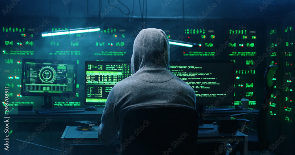 Fototapeta Rear view of incognito hacker using computer for organizing massive data breach attack on corporate servers. Secret location surrounded by displays, servers and cables.