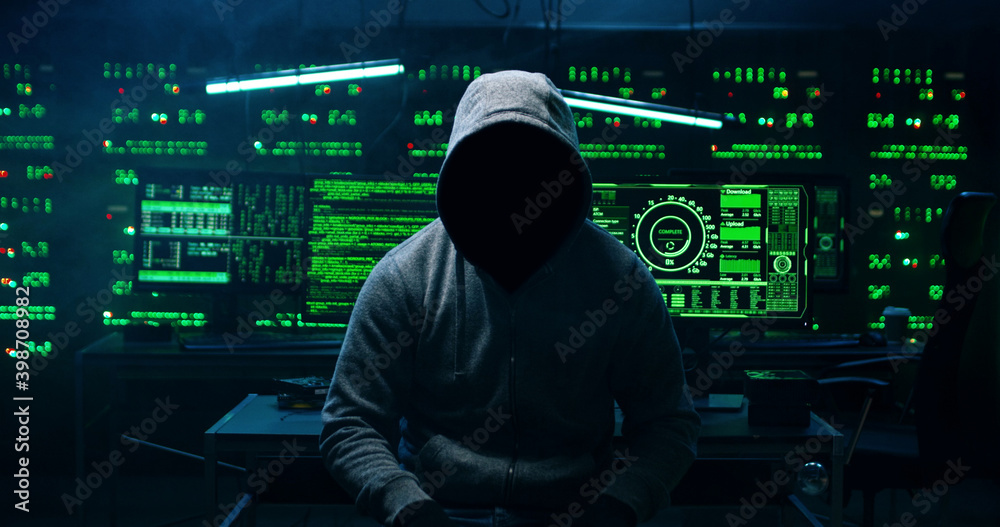 Fototapeta Portrait of  incognito hacker using computer for organizing massive data breach attack on corporate servers. Secret location surrounded by displays, servers and cables.