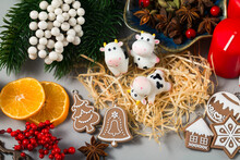 Three Cow Figures On A Christmas Background. Chinese New Year. Cute Smiling Toys, Gingerbread Decorations, Red Holly Berries, Tangerine Slices, Spices And Straw