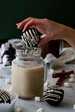 Woman's Hand Dropping Hot Chocolate Bomb Into Steaming Cup Of Milk. Marshmallows, Cinnamon Sticks And Presents In Background.