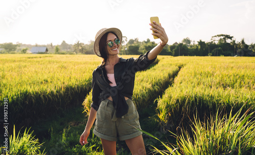 Cheerful Caucasian woman in trendy sunglasses using front smartphone camera for clicking selfie images, funny female influencer shooting travel vlog from Vietnam connecting to roaming internet