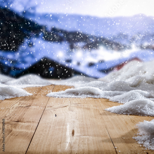 Fresh snow on a wooden table with an alpine view of the mountains