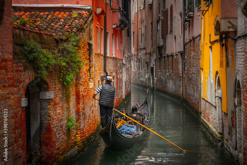 Tablou Canvas Venetian gondolier punting gondola through green canal waters of Venice Italy