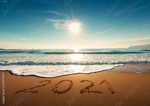 Fototapeta Beautiful sunrise over the sea. Happy New Year 2021 written on seashore. obraz