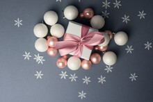 White Gift With Pink Ribbons. Gift Box Isolated On Gray Background With Snowflakes.Christmas Gift Boxes On Gray Background. Beautiful Christmas Background With Shiny Balls And Ribbons In Pink Color.