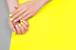 Stylish trendy female manicure. Beautiful young woman's hands on gray and yellow background.