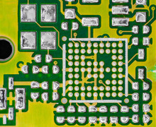 Front Photo Of A Yellow And Green Electric Circuit, With Shiny Silver Tin Solders, Devoid Of All Electronic Components.