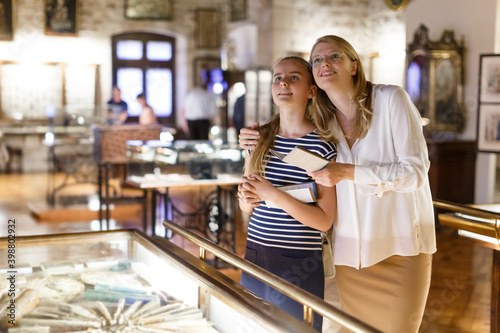 Canvas Print Young woman visitor with daughter looking to art objects under glass with guide