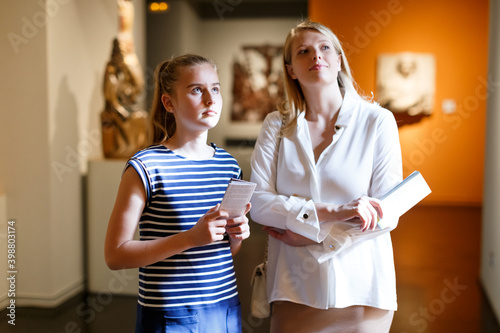 Valokuva Girl with woman looking with interest at ancient sculptures in museum, using gui