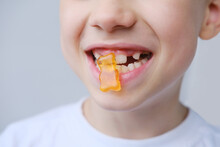 Boy, Kid Holds In His Mouth And Eats Gelatinous Sweets, Gummy Bear, Concept Of Children's Delicacy, Healthy And Unhealthy Food, Halal Food