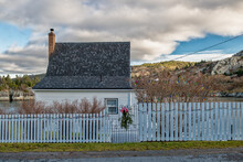 St. John's, Newfoundland, Canada - December 2020: A Small Vintage White Wooden Cottage Surrounded By A Wooden White Picket Fence That Has Decorations For Christmas: Lights, Wreath And Garland.
