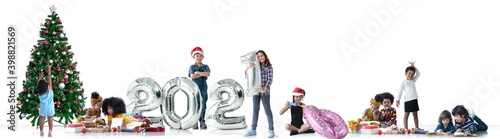 Fototapeta Children of different color and races have fun with metallic silver number balloons and Christmas trees, a diverse group of children, 2021 Happy new year, white background obraz