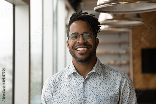 Fototapeta Profile picture of smiling young African American man in glasses pose in own home apartment. Close up headshot portrait of happy millennial biracial male renter or tenant in spectacles show optimism. obraz