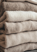 Cozy Milky Beige And White Natural Wool Sweaters, Folded On A White Background Close-up. Clothes Made Of Merino Wool, Alpaca, Natural Eco-fabrics. The Concept Of Conscious Consumption. Flat Lay