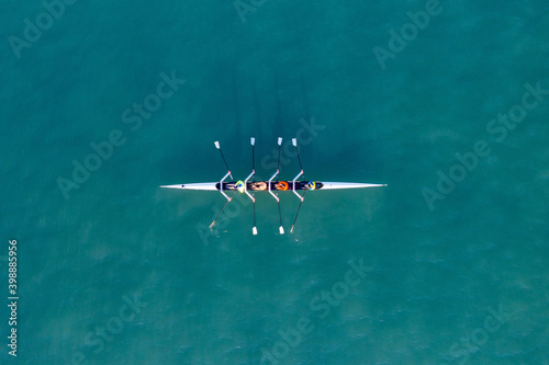 Valokuvatapetti Sport Canoe with a team of four people rowing on tranquil water, Aerial view