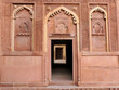 India - Uttar Pradesh - Agra - Agra Fort - A lofty window capped by an onion-shaped arch with carved details in red sandstone.