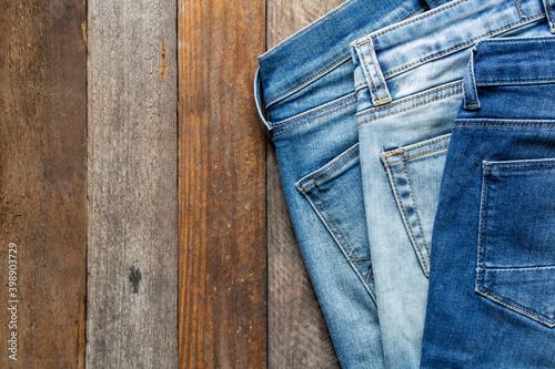 Fototapeta blue jeans on wooden surface background obraz