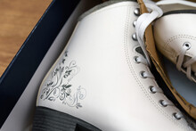 A Pair Of New White Figure Skates For Women In The Opened Box. The Box Lies On A Light Brown Wooden Background. Selective Focus.