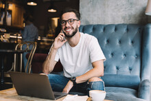 Funny Male Programmer In Optical Spectacles Smiling During Positive Cellphone Conversation For Discussing Web Networking, Joyful Caucaisan Blogger 20s Using 4g Internet For Calling And Talking