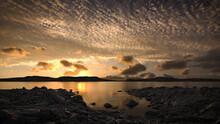 Peaceful Lake Scene At Sunset Or Sunrise With Scattered Clouds Reflecting In The Still Water. A Calm, Tranquil And Serene, Natural Landscape.