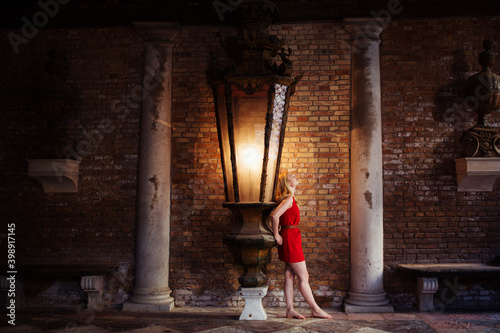 woman standing under a big lamp