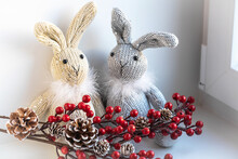 Two Toy Rabbits And A Christmas Decoration A Branch With Cones And Berries On The Windowsill