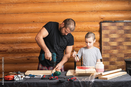 Father and son together make a wooden birdhouse in the workshop Fotobehang