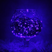 Dark Blue, Glittering, Christmas And New Year Interior Decor With A Chain Of Blue Led Lights Placed In A Large Glass Vase, Which Stands On A Long- Fur Soft Base At Night