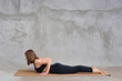 Sporty beautiful young woman in black sportswear doing easy variation of cobra asana, Sphinx Pose, baby Cobra posture, Ardha bhudjangasana Bhujangasana