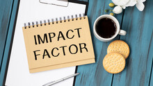 IMPACT FACTOR Words Is Written In A Notebook With A Marker, Calculator, Clamps And Cactus. Business Concept